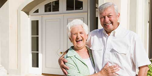 An elderly couple smile while standing outside of a home.