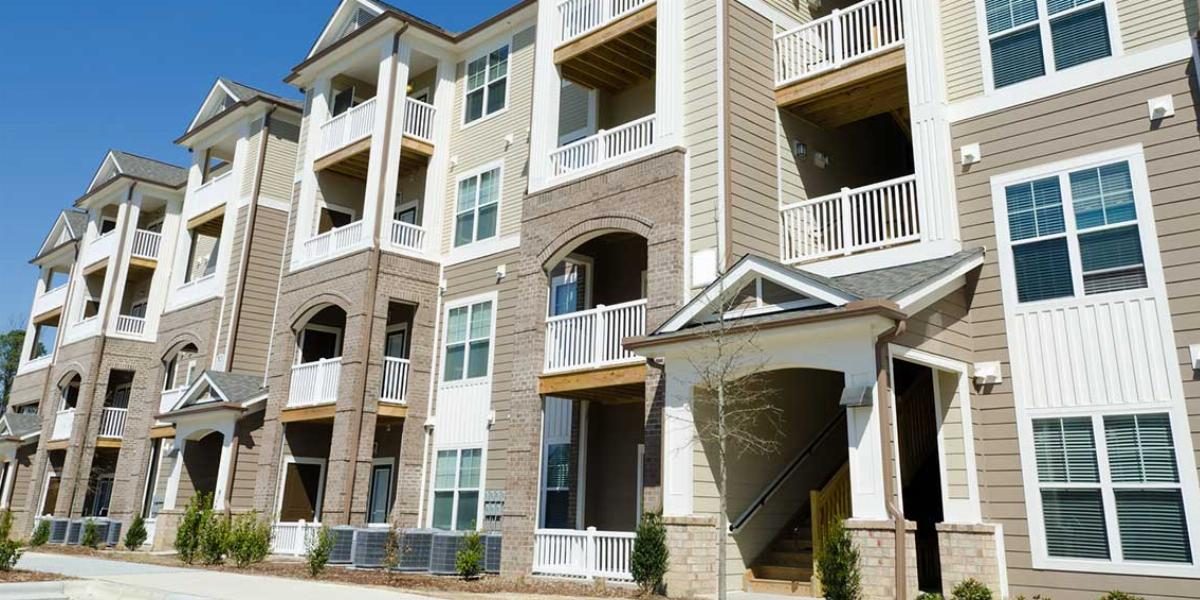Outside View of Apartment Complex with Neutral Paint and White Window Trim and Balconies.