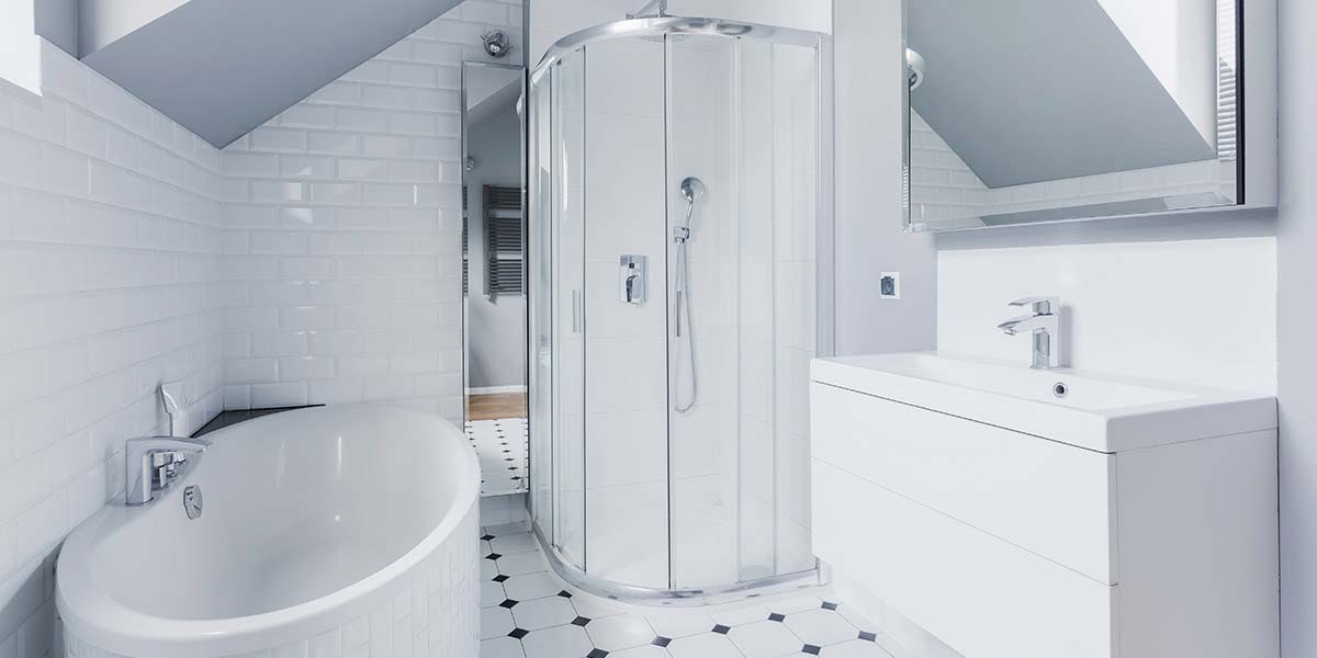 small bathroom with white tile and sloped ceiling