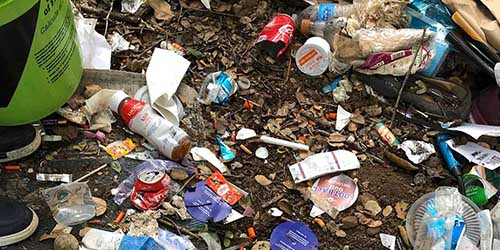 Ground heavily littered with food wrappers, plastic bottles and other trash.