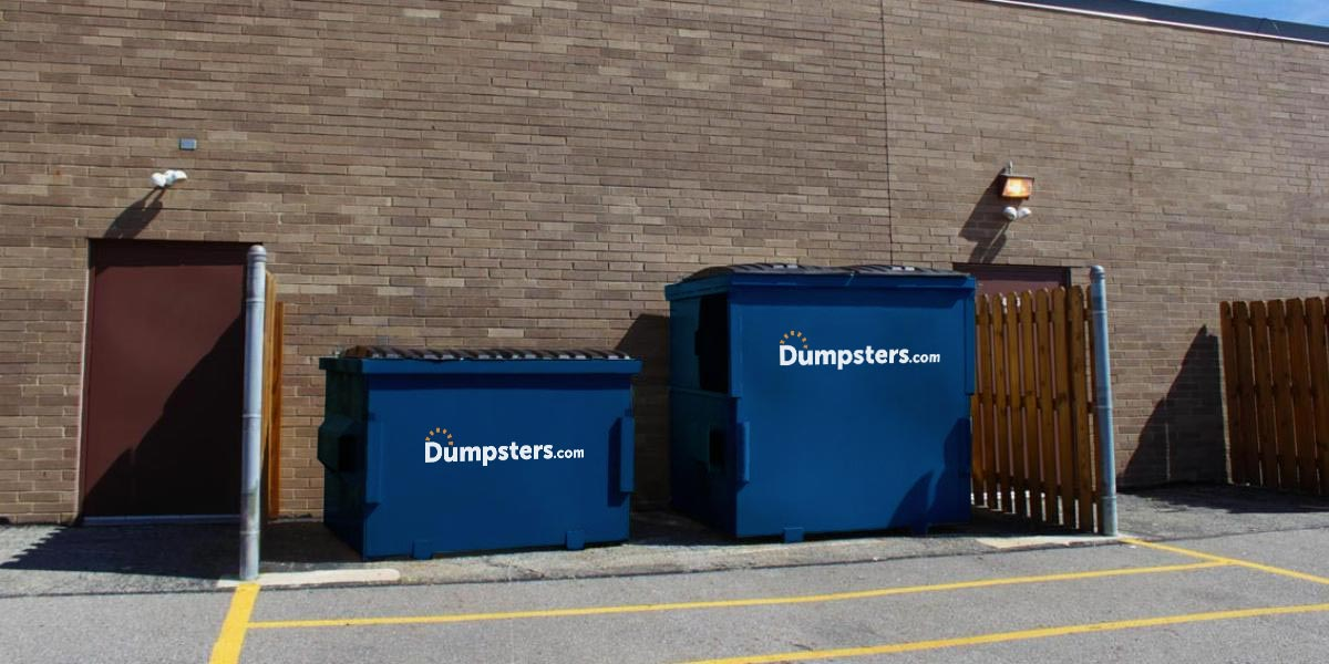 Two front load dumpsters in a commercial dumpster enclosure.