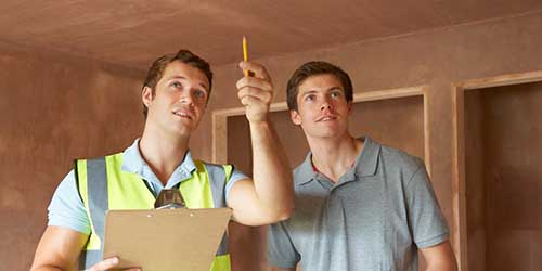 A Home Inspector Pointing Out Potential Repairs to a Home Buyer.