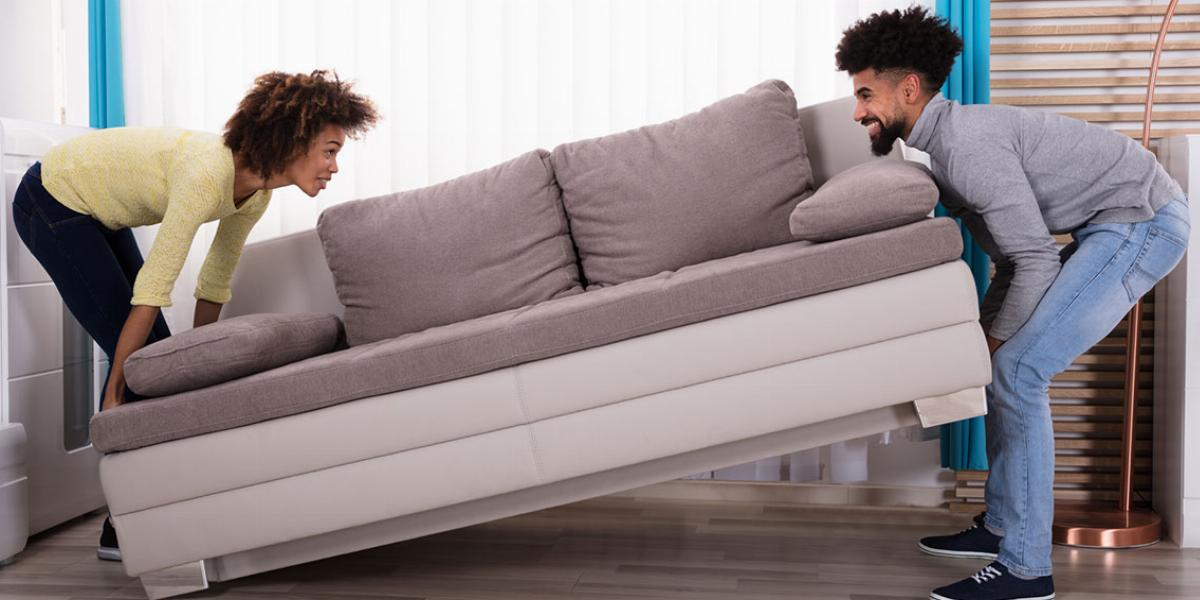 Young Man and Woman Smiling at Each Other While Bending Their Knees to Lift a Gray Couch