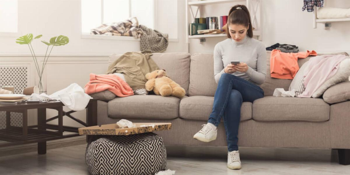 Woman Looking at Her Phone While Sitting on a Cluttered Couch