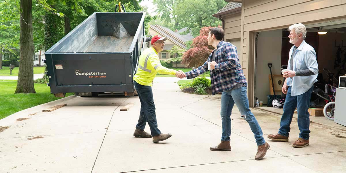 Dumpster.com Roll Off Truck Driver Matt Snyder Shakes Hands With a Customer During a Roll Off Dumpster Delivery.