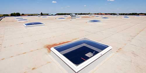 Flat Roof of an Industrial Building Under a Blue Sky.