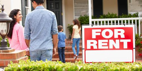 Family of four walking into home with for rent sign