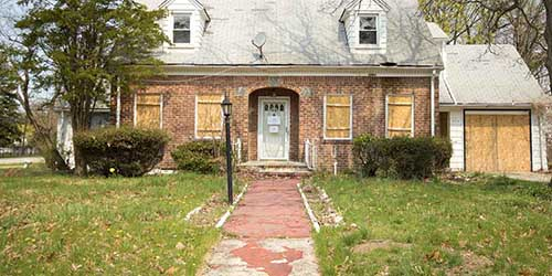 A Foreclosed Property with an Overgrown Yard and Boarded Windows.
