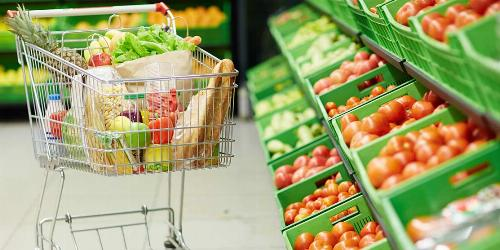 Full Shopping Cart Next to Green Bins of Produce at a Grocery Store
