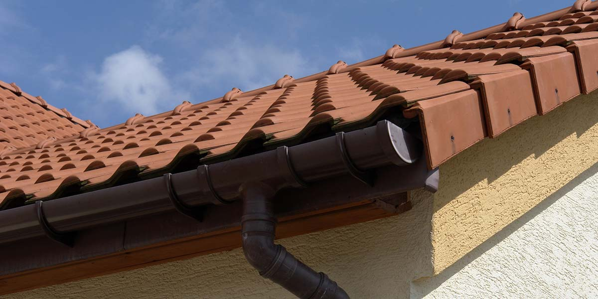 Brown Gutters and Downspout Attached to House with Clay Roof Tiles.