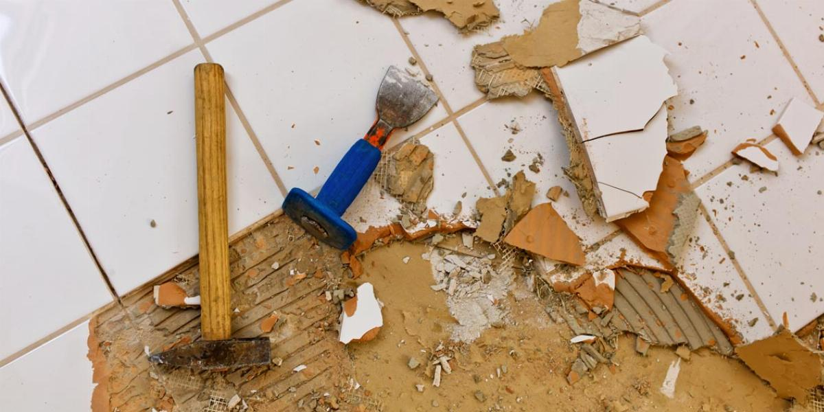 Hammer and Chisel Being Used to Remove Floor Tile