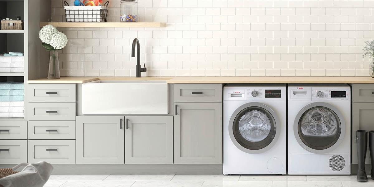 Laundry Room With White Appliances and Gray Cabinets.
