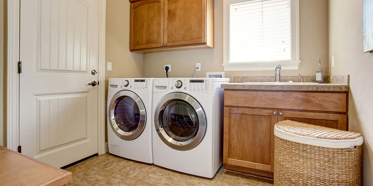 Laundry Room With White Appliances and Wood Cabinets.