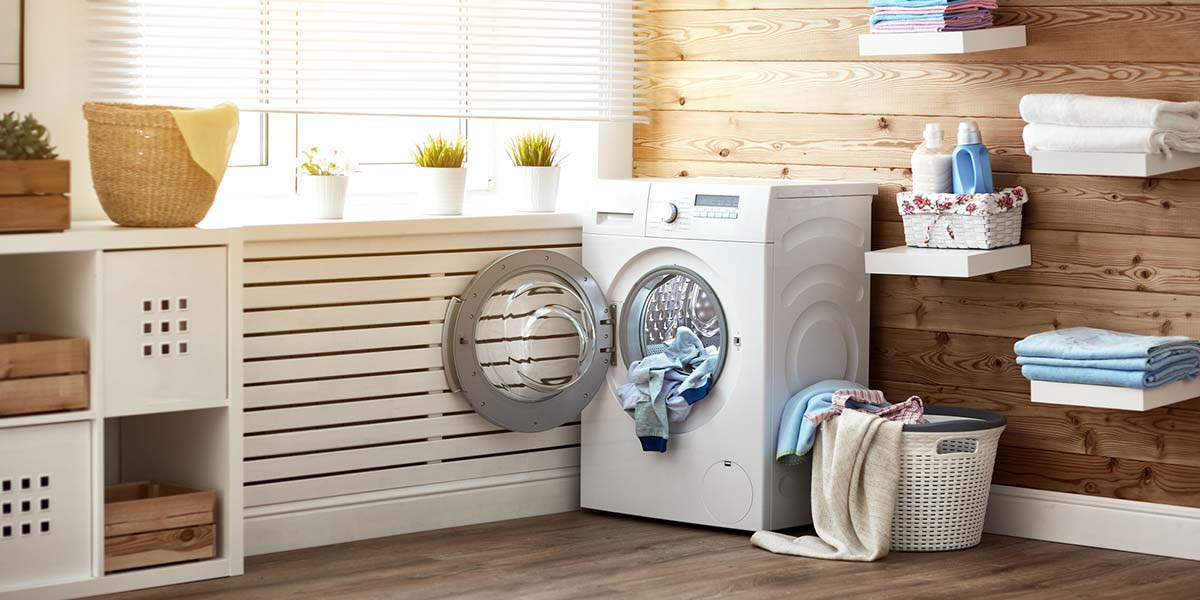 Spacious laundry room with window, floating shelves and wood floors and walls