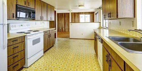 Retro-Style Kitchen With Wood Grain Cabinets and Yellow Patterned Linoleum Floor