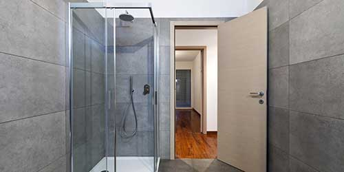 A modern shower with tile walls, glass doors and a fiberglass floor pan in room.