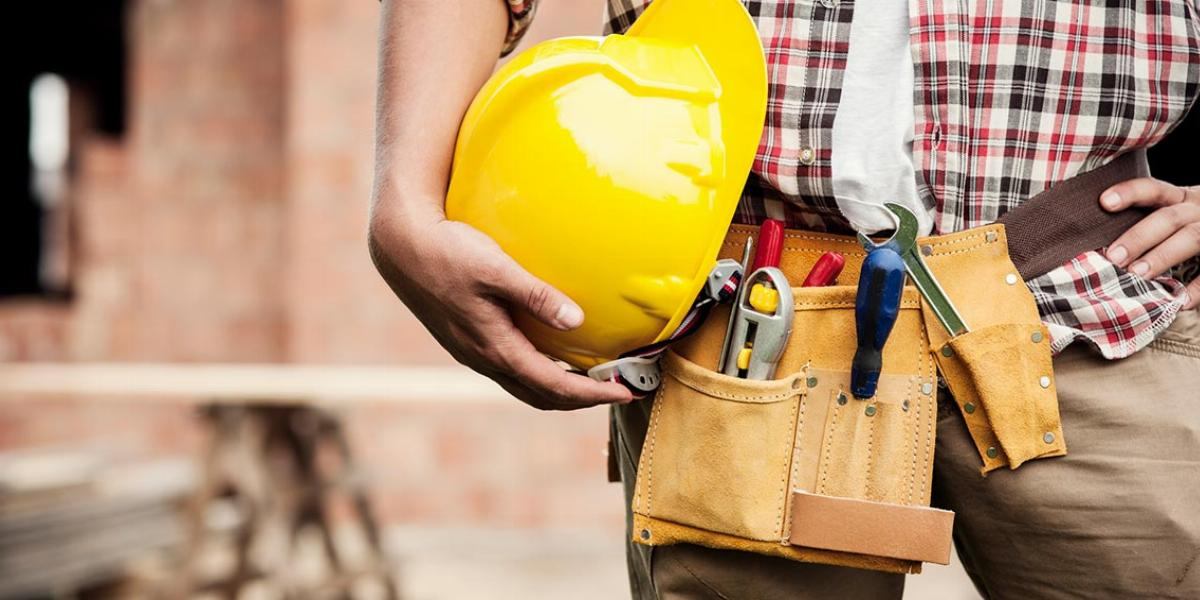 Construction Worker Holding Hard Hat With a Work Belt Around His Waist
