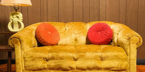 Yellow velvet sofa with red and orange pillows in front of 1970's style wood paneling