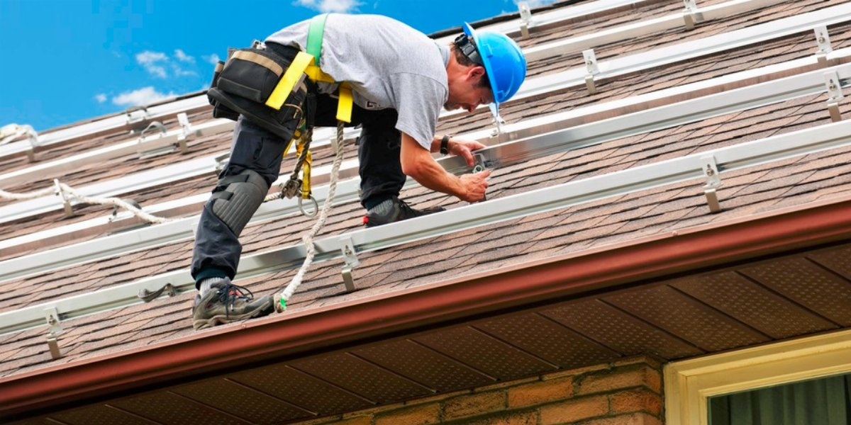 Man working on top of a roof wearing safety equipment.