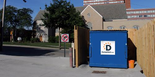 Commercial dumpster in an enclosure.