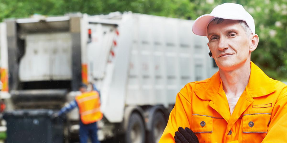 Garbageman in orange long-sleeve shirt with white hat and black gloves stands cross-armed in foreground as white garbage truck is loaded by another garbageman in the background.