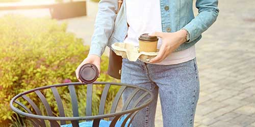 Woman Tossing Coffee Cup in Trash.