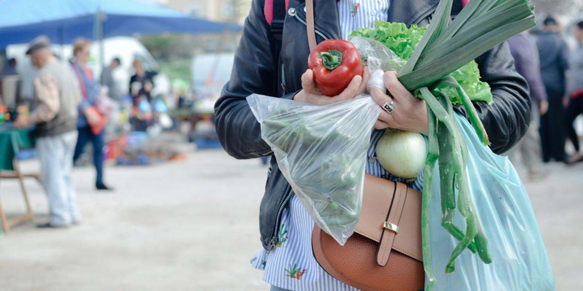 A customer holds vegetables and plastic grocery bags at a farmer's market.