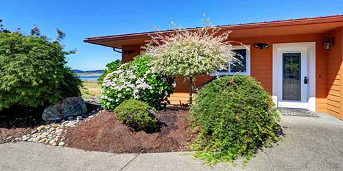 A xeriscape front yard featuring heavy hardscape use along with much and water conserving plants.