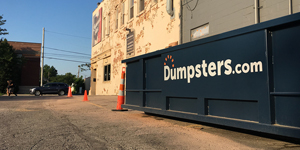 Side View of a Blue Dumpster With Dumpsters.com Logo Marked Off With Cones