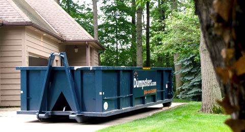Roll Off Dumpster in Residential Driveway Surrounded by Trees.