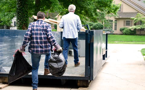 Two Men Loading Up a Roll Off Dumpster.
