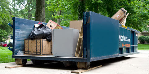 Roll Off Dumpster in Driveway Filled with Boxes and Other Household Junk.
