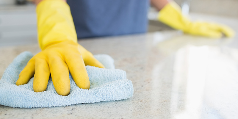 Person Cleaning Kitchen Countertops with Yellow Gloves and Blue Cloth