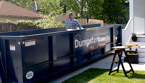 Man Standing Inside a Dumpsters.com Roll Off Container Outside in a Driveway Outside of a House