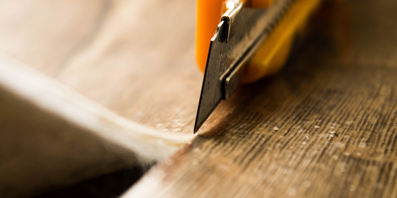 Close Up of a Utility Knife Cutting Through Brown Linoleum Flooring