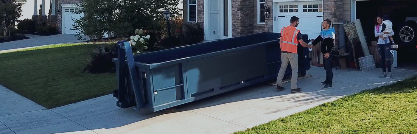 family thanking a driver for delivering a dumpster rental