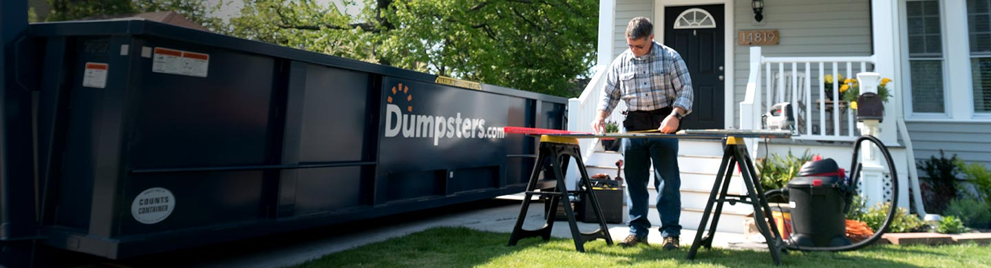 Contractor working outside with a dumpster.