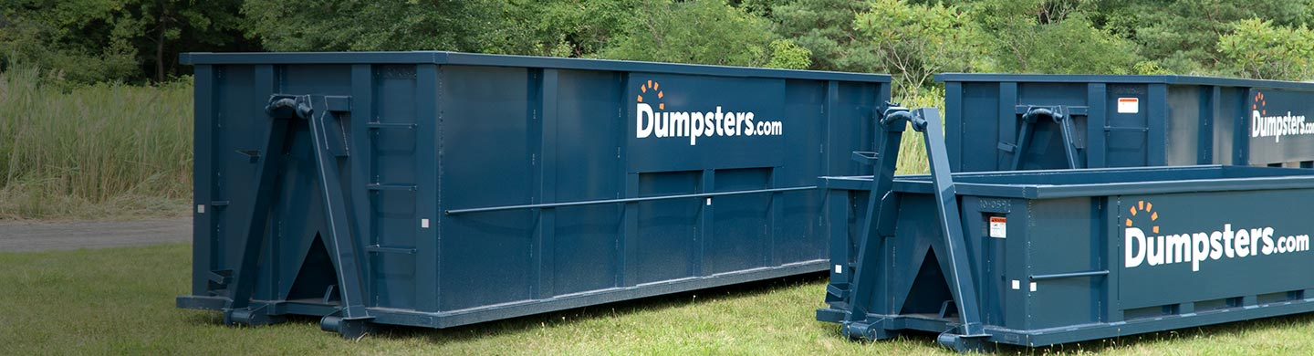 Several different dumpster sizes in grassy field
