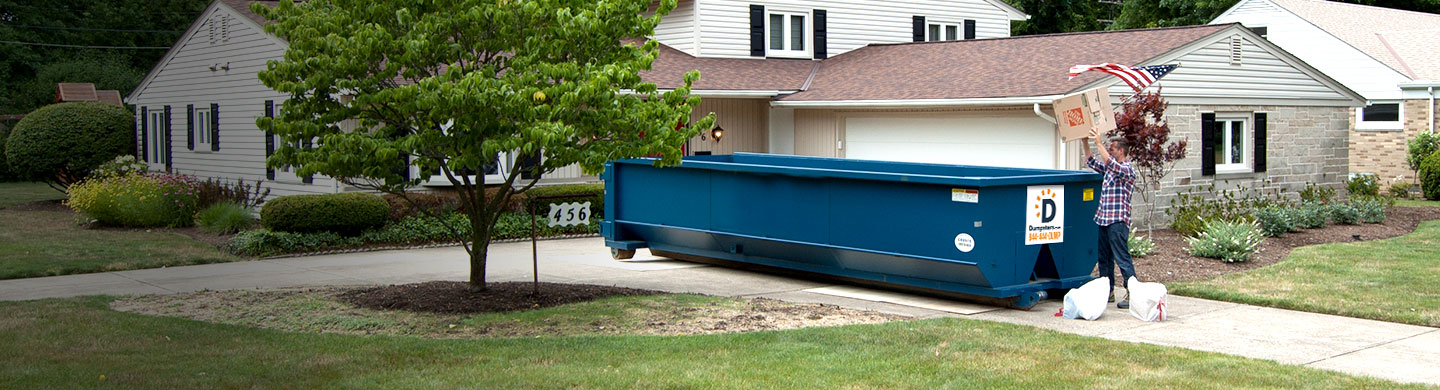 man loading a dumpster in a driveway