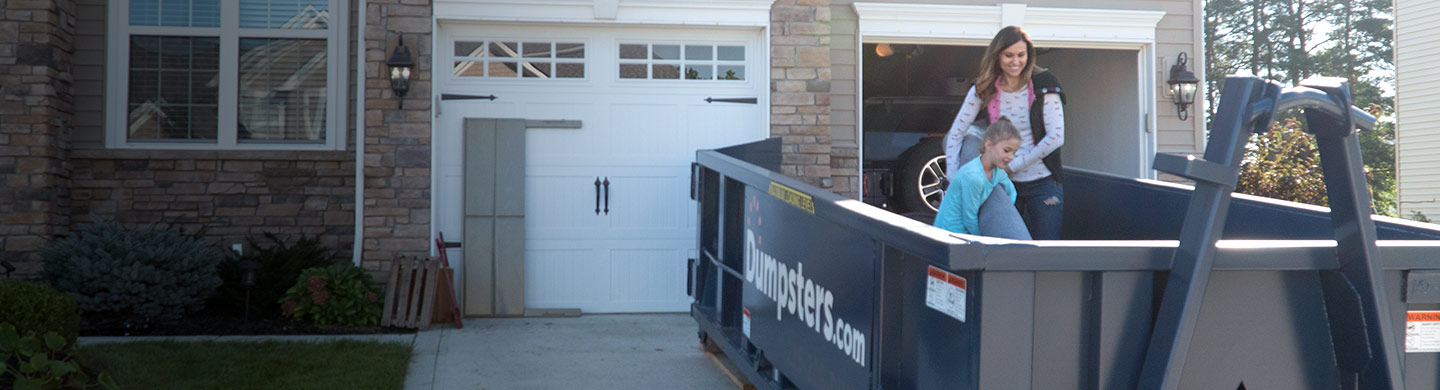 Mother and Daughter Loading Junk into Blue Residential Dumpster in Front of Nice House