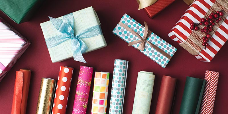 Tubes of Brightly Colored Wrapping Paper Below Wrapped Gifts