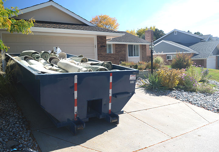 Roll Off Dumpster in Residential Driveway Full of Carpet.