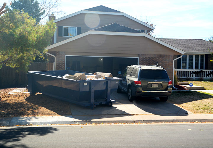 Roll Off Dumpster Near SUV in Residential Driveway.