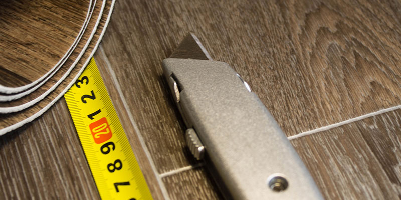 Tape Measure and Utility Knife Next to a Roll of Cut-Up Vinyl Flooring