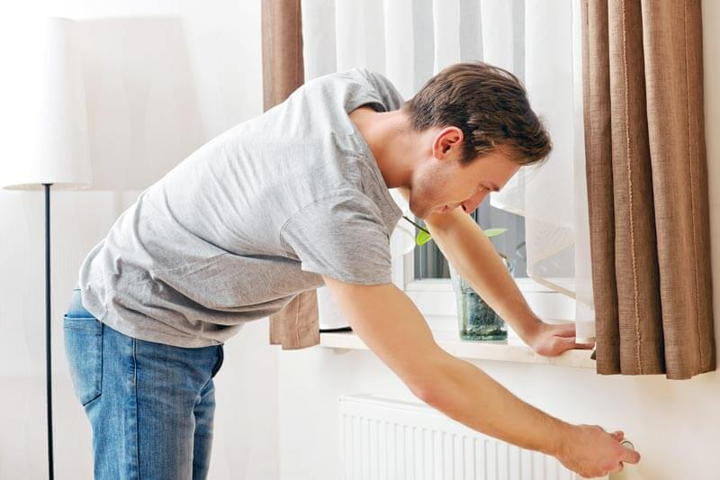 Man Adjusting a Thermostat