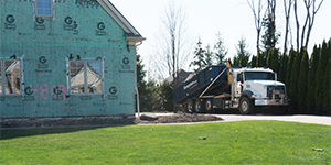 Truck Delivering a Blue Roll Off Dumpster to a House Under Construction