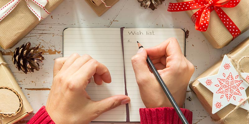 Person in Red Sweater Writing in a Notebook Surrounded by Holiday Gifts
