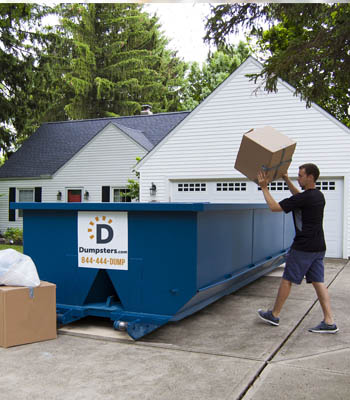 Homeowner tossing junk into a dumpster