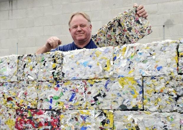 Man standing behind a wall of Byfusions recycled plastic blocks.