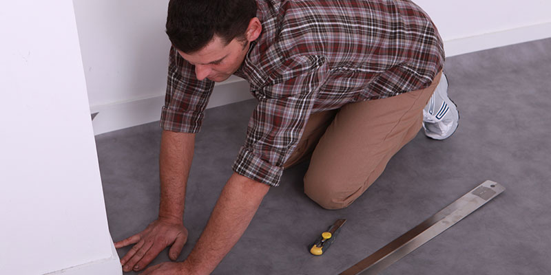 Man Kneeling and Pulling Gray Vinyl Flooring Away From Wall